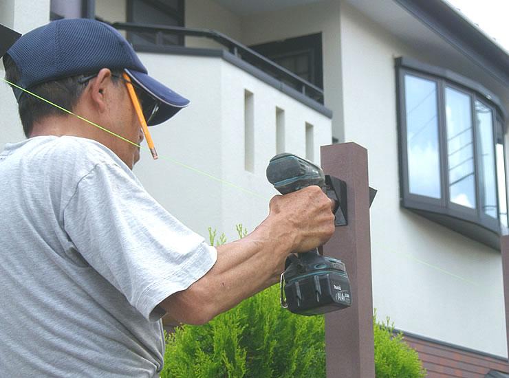 ポール固定金具を設置している風景