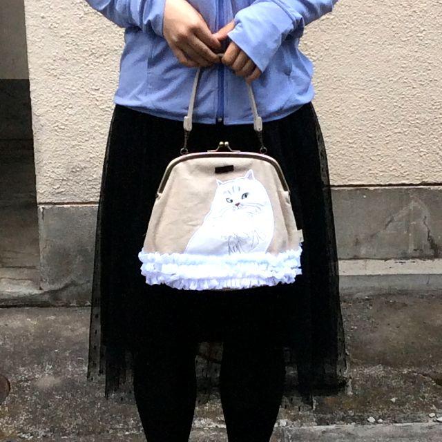ルートート白猫フリルがま口バッグの人間との大きさ比較の画像