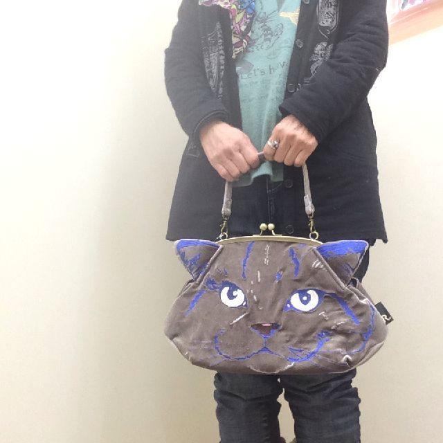 ルートート猫顔刺繡がま口バッグを手に下げた画像