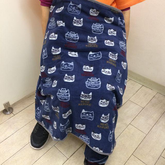 クスグルジャパンのネコザワさんのケース入りひざ掛けを膝に掛けた画像