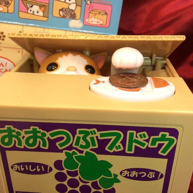 猫の貯金箱から猫が顔と手を出して、コインを盗ろうとしている画像