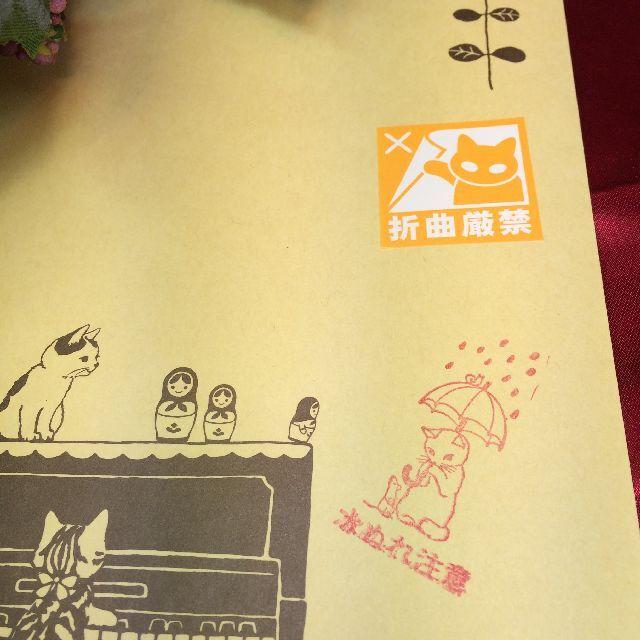 ねこケアマークシールmini折曲厳禁柄の黄色を封筒に貼った画像