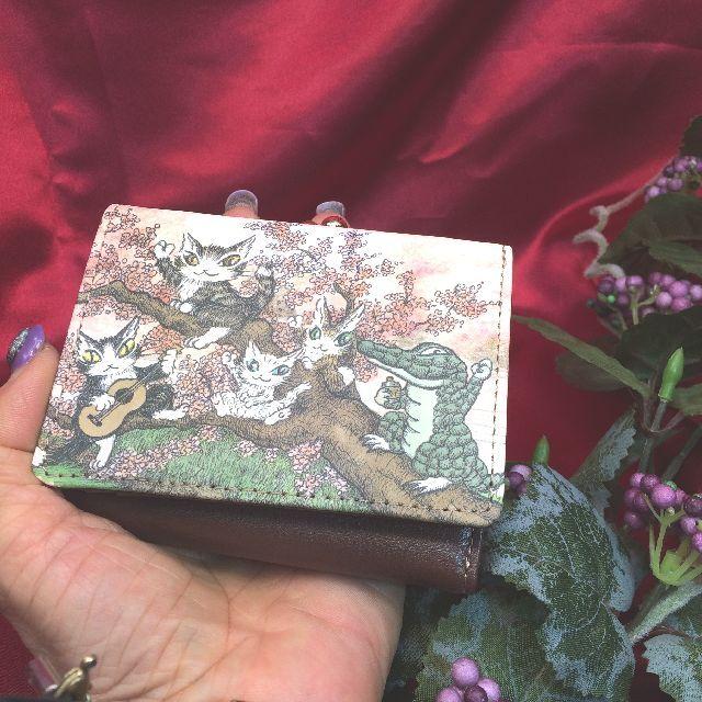 猫のダヤンのがま口三つ折り財布「永遠の桜」柄を手の平に載せた画像