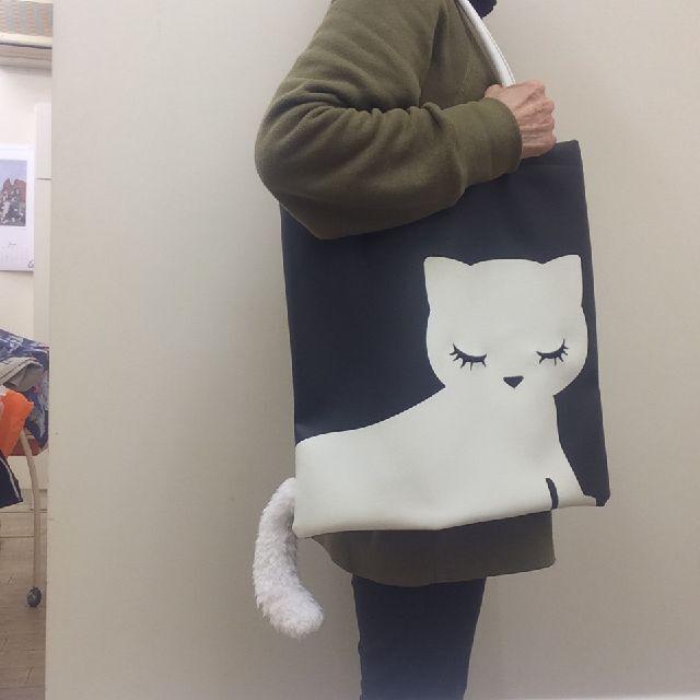 アディクトのおすましプーちゃんのシッポ付きトートバッグを肩に提げた画像