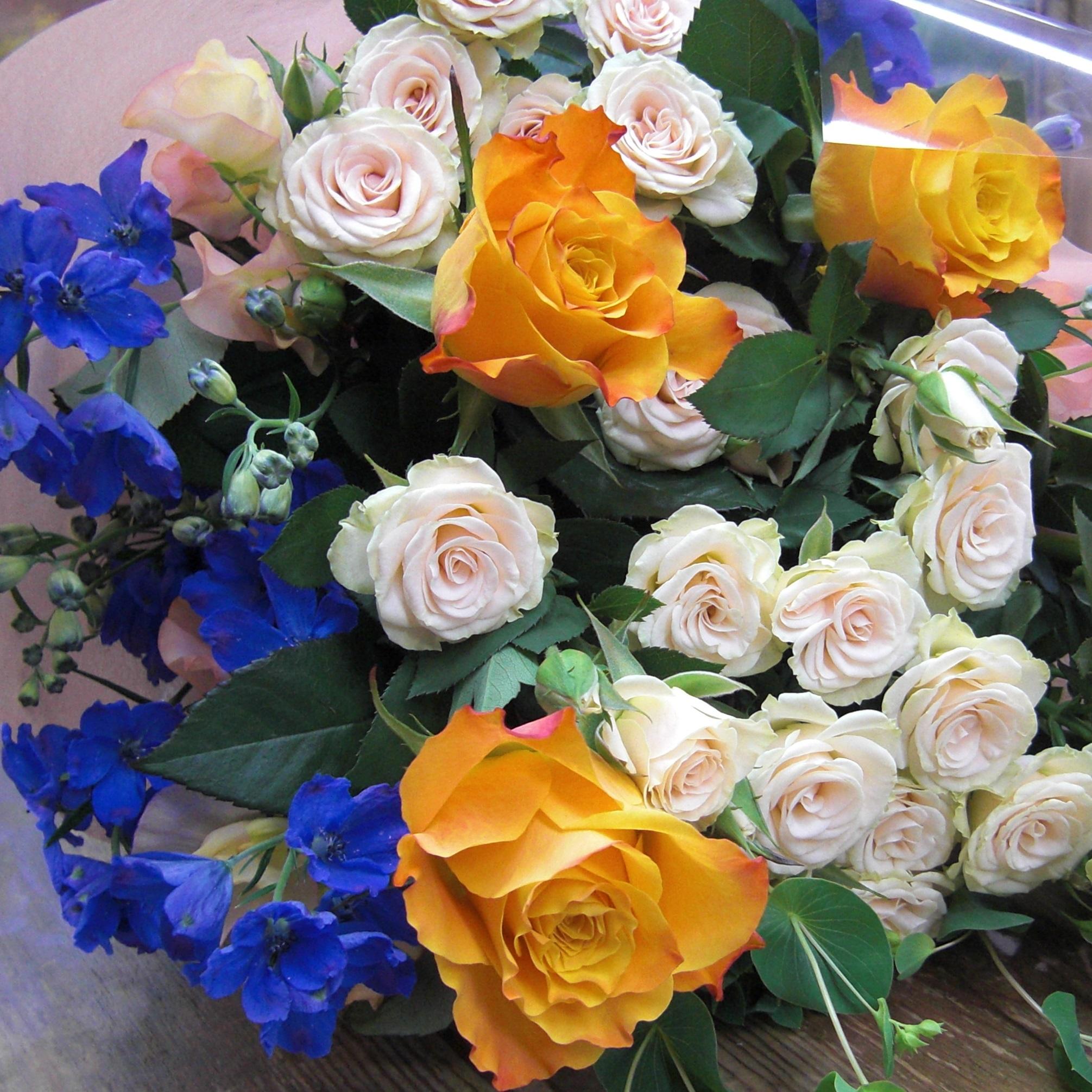 オレンジ色のバラとアクセントにブルーのデルフィニウムを使った花束