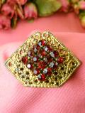 <英国コスチュームジェリー>キラキラ輝くレッドクリスタル金色の透かし模様が素晴らしい光のブローチ