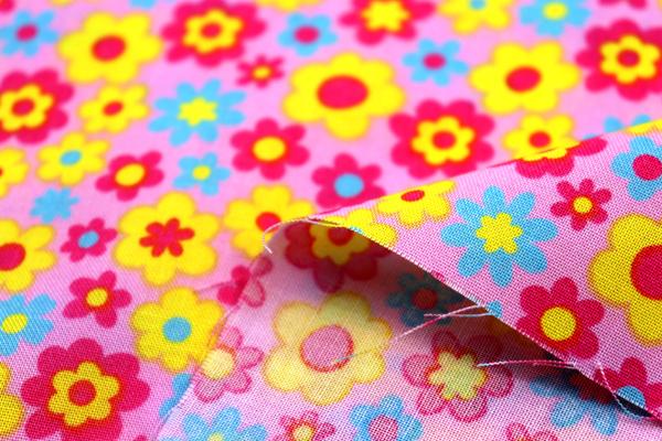 シーチング レトロ調フラワープリント ピンク地にきいろ・みずいろ・あかの花