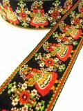 民族衣装を着てお花をたくさん抱えている女の子が織られている幅太のチロリアンリボン(2カラー)