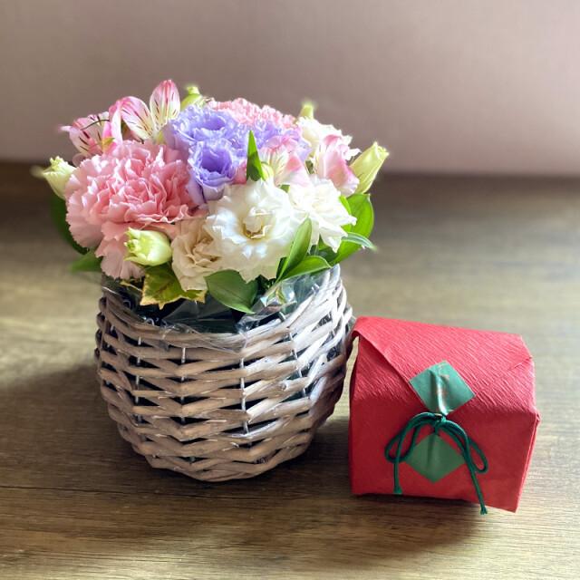 和菓子とお花の贈り物コロンとしたバスケットに入ったピンク系のフラワーアレンジメントとつちやの紅琳果