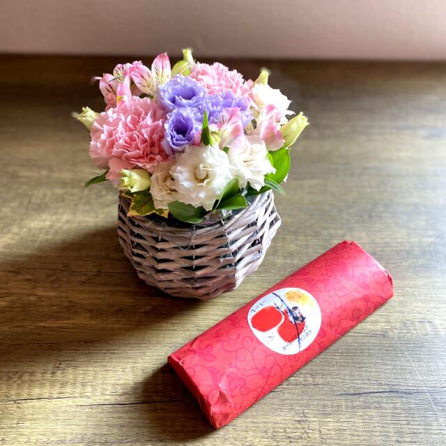 和菓子とお花の贈り物コロンとしたバスケットに入ったピンク系のフラワーアレンジメントとつちやの柿羊羹