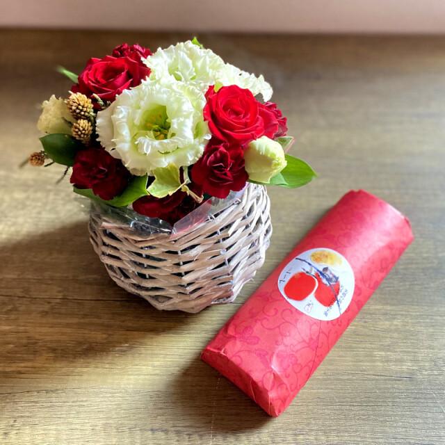 和菓子とお花の贈り物コロンとしたバスケットに入った赤と白のフラワーアレンジメントとつちやの柿羊羹