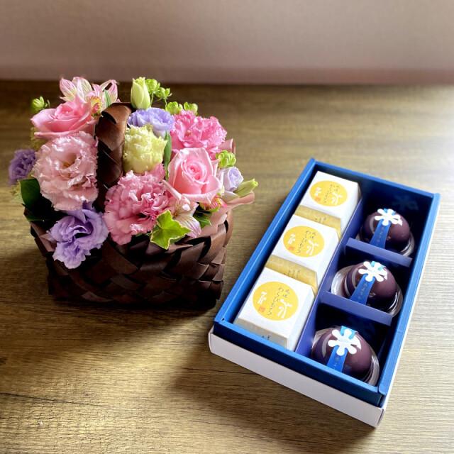 和菓子とお花の贈り物バスケットに入ったピンク系のフラワーアレンジメントとつちやの水ようかんとわらび餅の涼果詰め合わせ