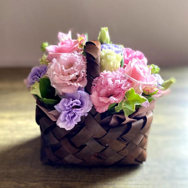 和菓子とお花の贈り物正面から見たバスケットに入ったピンク系フラワーアレンジメント