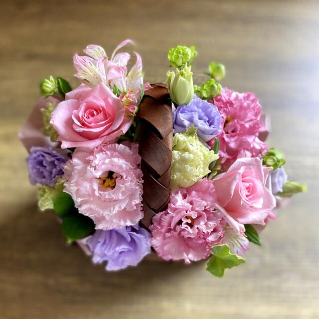 和菓子とお花の贈り物上から見たバスケットに入ったピンク系フラワーアレンジメント