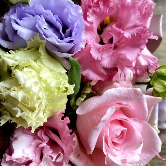 和菓子とお花の贈り物バスケットに入ったピンク系のフラワーアレンジメントのアップ