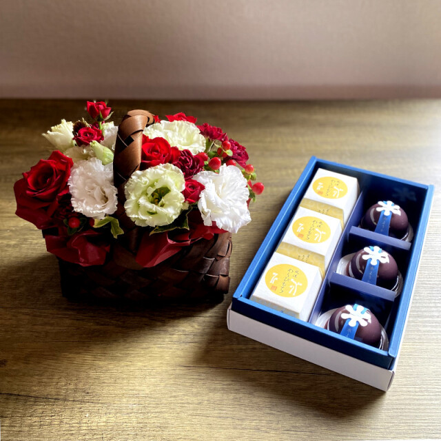 和菓子とお花の贈り物バスケットに入った赤と白のフラワーアレンジメントとつちやの水ようかんとわらび餅の涼果詰め合わせ