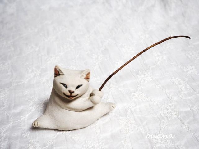 釣り竿を持つ白猫