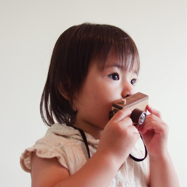 木のおもちゃカメラをさげる女の子