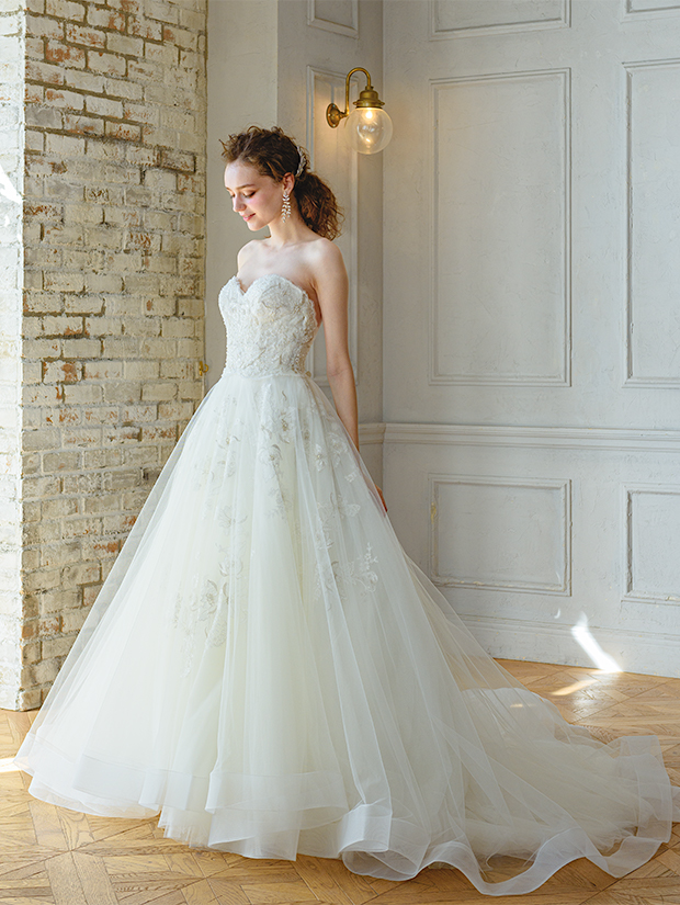 ウェディングドレスを着て笑みを浮かべる花嫁